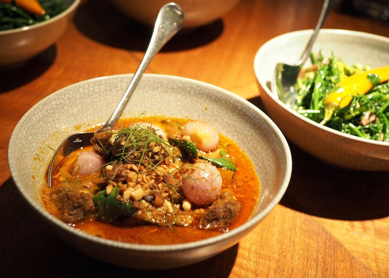 A bowl of red Penang curry with peanuts, shallots and Thai basil with some other dishes int he background - from Nahm, Bangkok