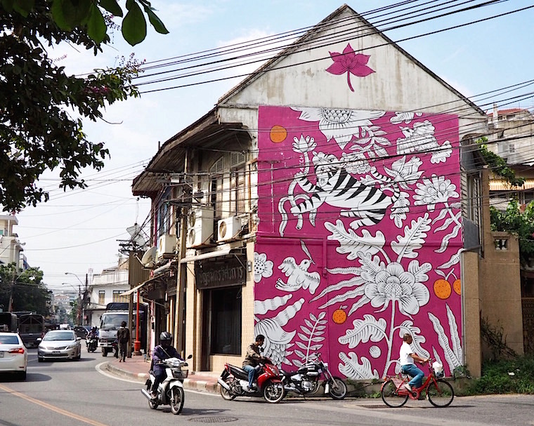 Illustrations of a cat and plants on a bright pink background covering the side of a two-storey house. Painted by Aitch for the BUKRUK II festival