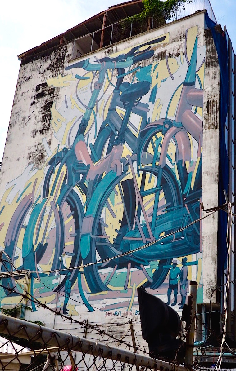 Huge bikes span a wall in Bangkok, painted for the BUKRUK festival