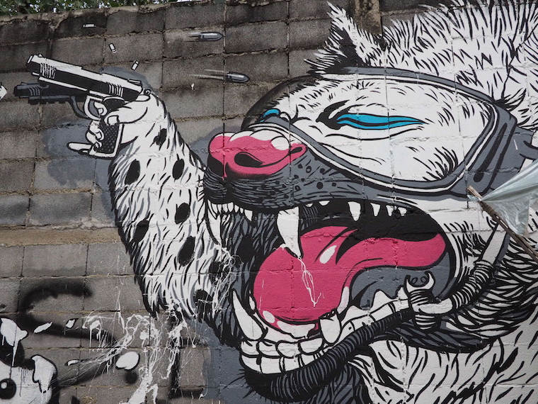 A pink, white and black leopard fires a gun - street art by Bonus TMC