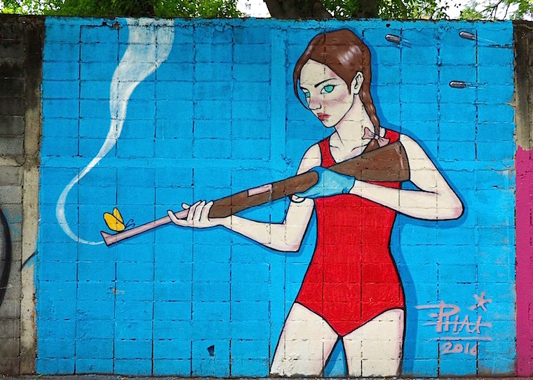 A woman in a red bathing suit holds a smoking shotgun . A yellow butterfly sits on the end. The background is a vivid blue - painted by Phai
