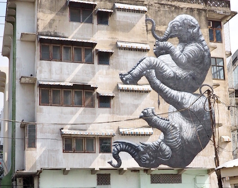 Two elephants tumble down the side of a building, created by ROA for the BUKRUK festival