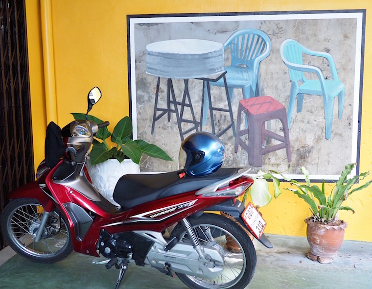 A mural of some chairs and a table sits behind a red scooter.