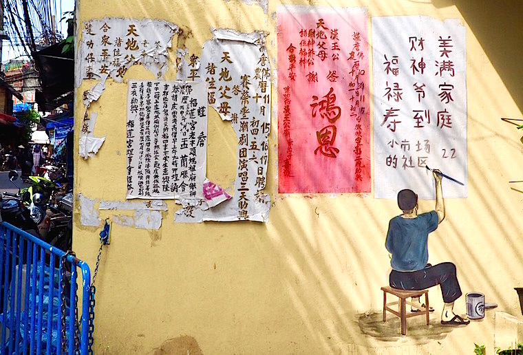 A man sits on a stool, writing in Chinese - street art in BAngkok