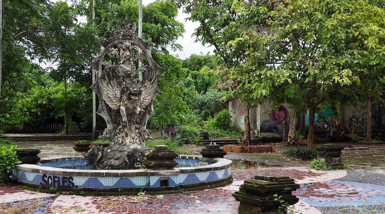 A once ornate fountain of Balinese barong with dry leaves and green trees around it found at Taman festival, an abandoned theme park in Bali